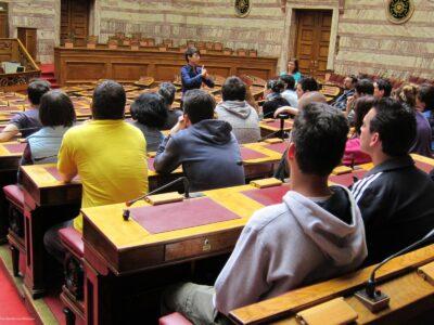 Η φωτογραφία δείχνει ένα μέρος της κεντρικής αίθουσας συνεδριάσεων της Βουλής. Σε πρώτο πλάνο φαίνονται από πίσω πολλοί νεαροί επισκέπτες καθισμένοι στα έδρανα των βουλευτών. Στο βάθος διακρίνεται μία ξεναγός που απευθύνεται στο ακροατήριο, ενώ πίσω της φαίνεται μέρος της έδρας της Βουλής.