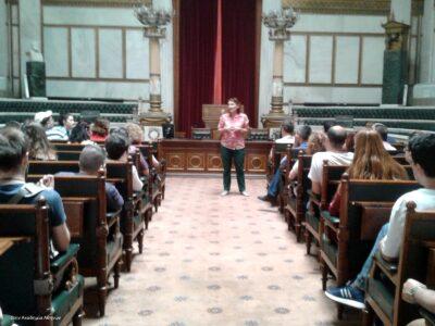 Η μεγάλη αίθουσα της Ακαδημίας Αθηνών είναι περίτεχνα διακοσμημένη με ορθομαρμάρωση, κίονες, βάσεις με προτομές, ξυλόγλυπτη έδρα και πολλές σειρές ξύλινων καθισμάτων με πράσινη δερμάτινη ταπετσαρία. Τα καθίσματα είναι γεμάτα ακροατές που παρακολουθούν την ξεναγό, η οποία στέκει στο βάθος του διαδρόμου που χωρίζει τα καθίσματα.