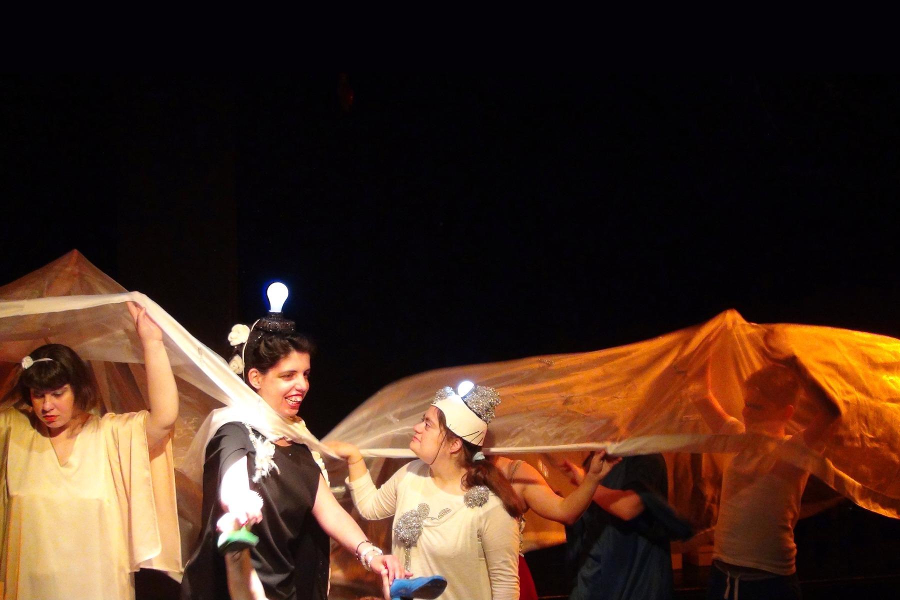 Αγόρια και κορίτσια ντυμένα με θεατρικά ρούχα κρατούν όρθια ένα πολύ μεγάλο λεπτό γυαλιστερό ύφασμα που τα σκεπάζει σαν πέπλο. Το πέπλο που παίρνει διάφορα χρώματα από τους κίτρινους προβολείς, αφήνει ακάλυπτα τρία κορίτσια. Τα δύο φοράνε από έναν αναμμένο γλόμπο στο κεφάλι τους και κοιτιούνται γελώντας, ενώ το τρίτο κρατάει το ύφασμα ψηλά και κοιτάζει κάτω.