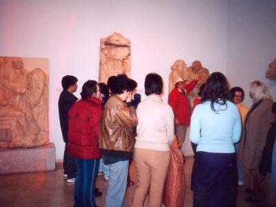 Στην ευρύχωρη αίθουσα του μουσείου διακρίνονται γλυπτά και ανάγλυφα επιτύμβια μαρμάρινα εκθέματα. Μία ομάδα νέων με γυρισμένη την πλάτη παρακολουθεί τον ξεναγό να τους δείχνει κάτι με σηκωμένο χέρι.
