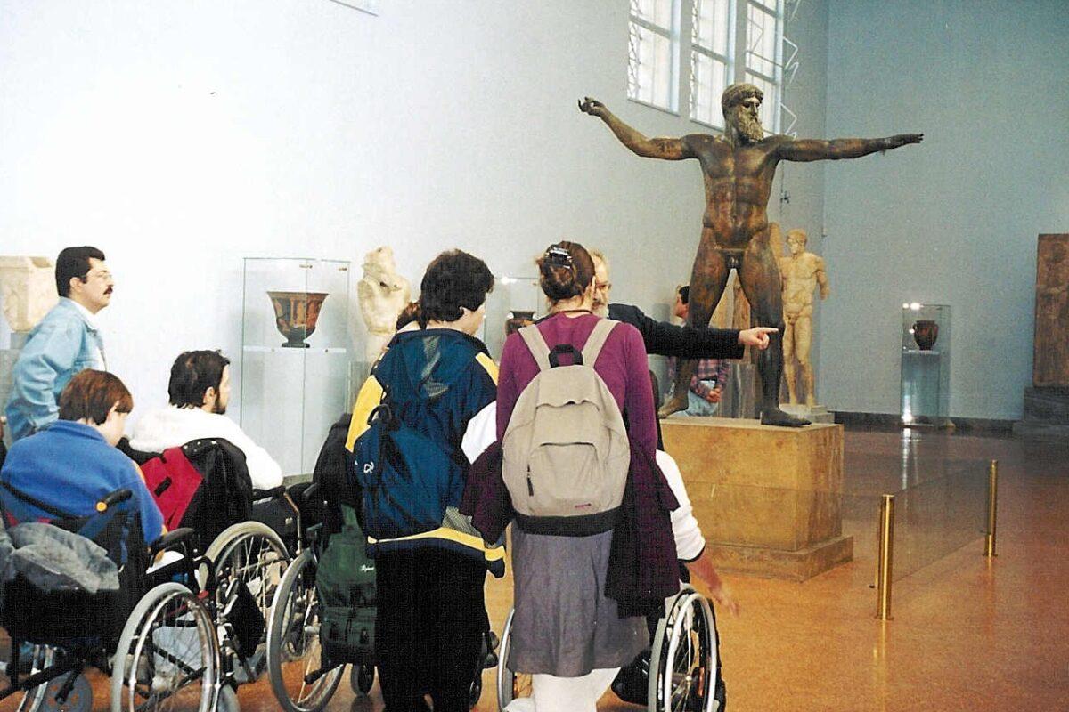 Στο κέντρο μεγάλης αίθουσας μουσείου ορθώνεται  πάνω σε υψηλή μαρμάρινη βάση μεγαλόσωμο μπρούτζινο αρχαίο άγαλμα. Το γλυπτό παριστάνει έναν μυώδη γυμνό άνδρα με πόδια και χέρια σε διάταση.  Τέσσερις επισκέπτες καθισμένοι σε αναπηρικά αμαξίδια και τρεις όρθιοι κοιτάζουν προς το γλυπτό. Ξεχωρίζει το  χέρι του ξεναγού που τους δείχνει κάτι.