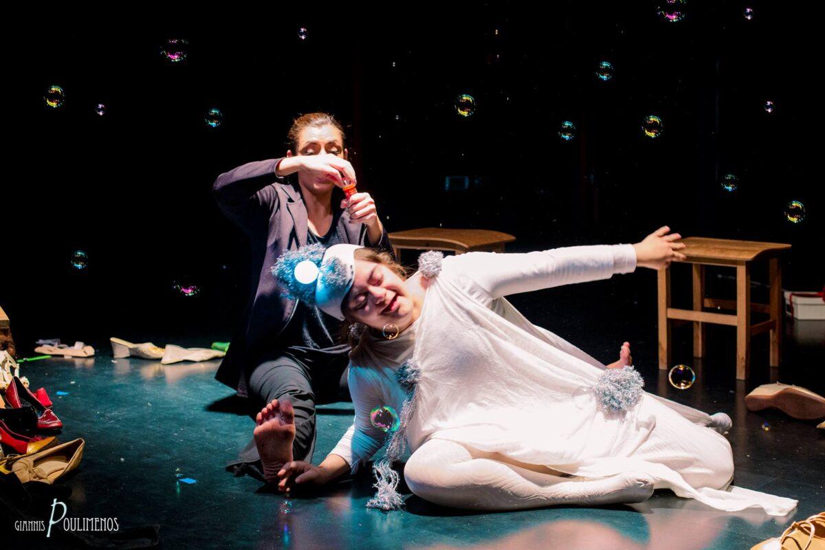 Δυο κοπέλες στο πάτωμα η μία καθιστή και ξυπόλητη φοράει μπλε κουστούμι και κρατάει ένα μπουκαλάκι. Η άλλη φοράει λευκό θεατρικό φόρεμα και έχει έναν αναμμένο γλόμπο στερεωμένο στο κεφάλι της. Γέρνει χαμογελώντας στο πλάι με χορευτική κίνηση.
