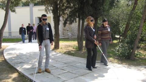 Σε δενδρόφυτο χώρο πάνω σε φαρδύ πλακόστρωτο περπατάνε 3 άτομα. Είναι δύο γυναίκες και ένας άνδρας από τους οποίους οι δύο έχουν καλυμμένα τα μάτια τους με μαύρες μάσκες και αγγίζουν το κράσπεδο με λευκό μπαστούνι. Ο άνδρας προχωρεί μόνος του ανιχνεύοντας το έδαφος ενώ η γυναίκα προχωράει διστακτικά έχοντας δίπλα της συνοδό χωρίς μάσκα. Πίσω τους και σε κάποια απόσταση διακρίνεται άλλο ένα ζευγάρι, όπου ο ένας μόνο φοράει μάσκα και κρατάει λευκό μπαστούνι.