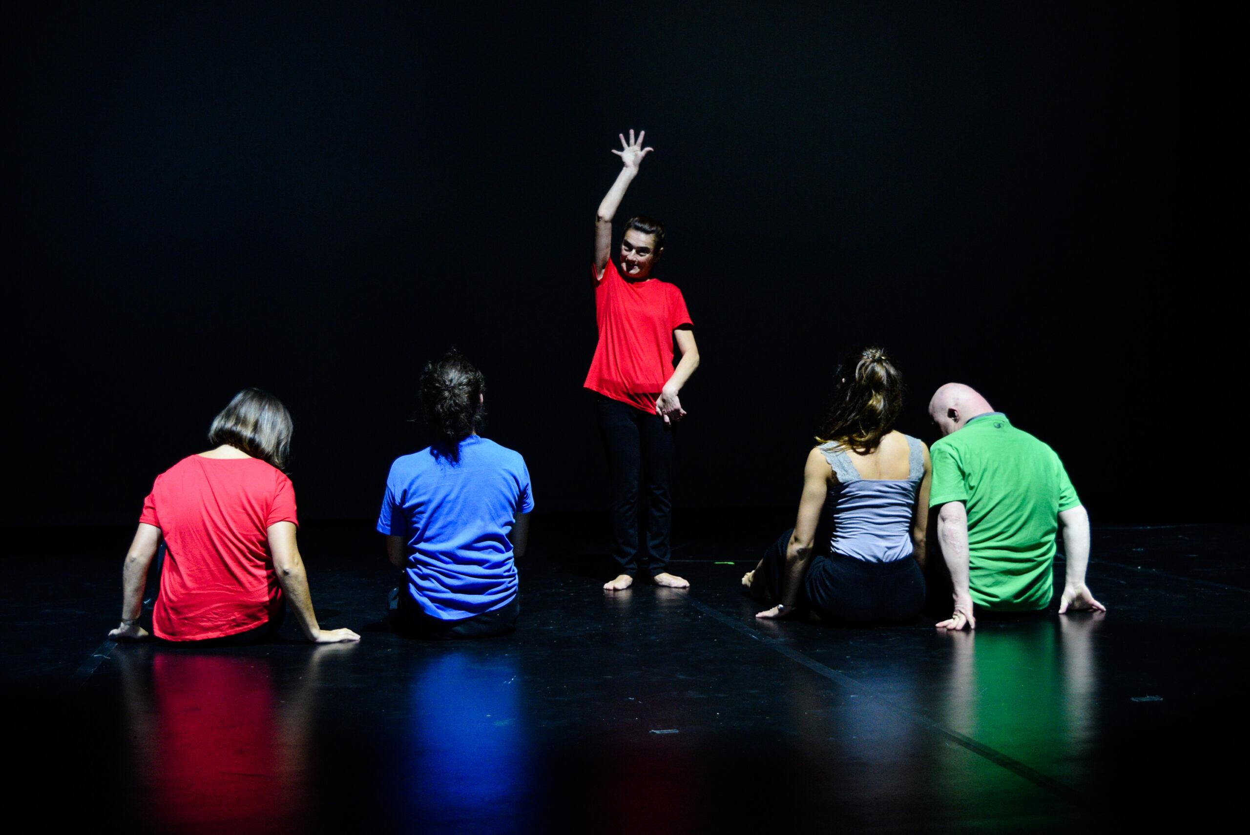 Τέσσερις χορευτές τρεις κοπέλες και ένας άνδρας είναι καθισμένοι δύο δύο στο γυαλιστερό πάτωμα της σκηνής με την πλάτη προς το κοινό. Μία χορεύτρια κοιτάζοντας όρθια το κοινό έχει το ένα χέρι κάτω και το άλλο ψηλά με δάκτυλα ανοιχτά. Όλοι φοράνε σκούρα παντελόνια και διαφορετικά μονόχρωμα μπλουζάκια.