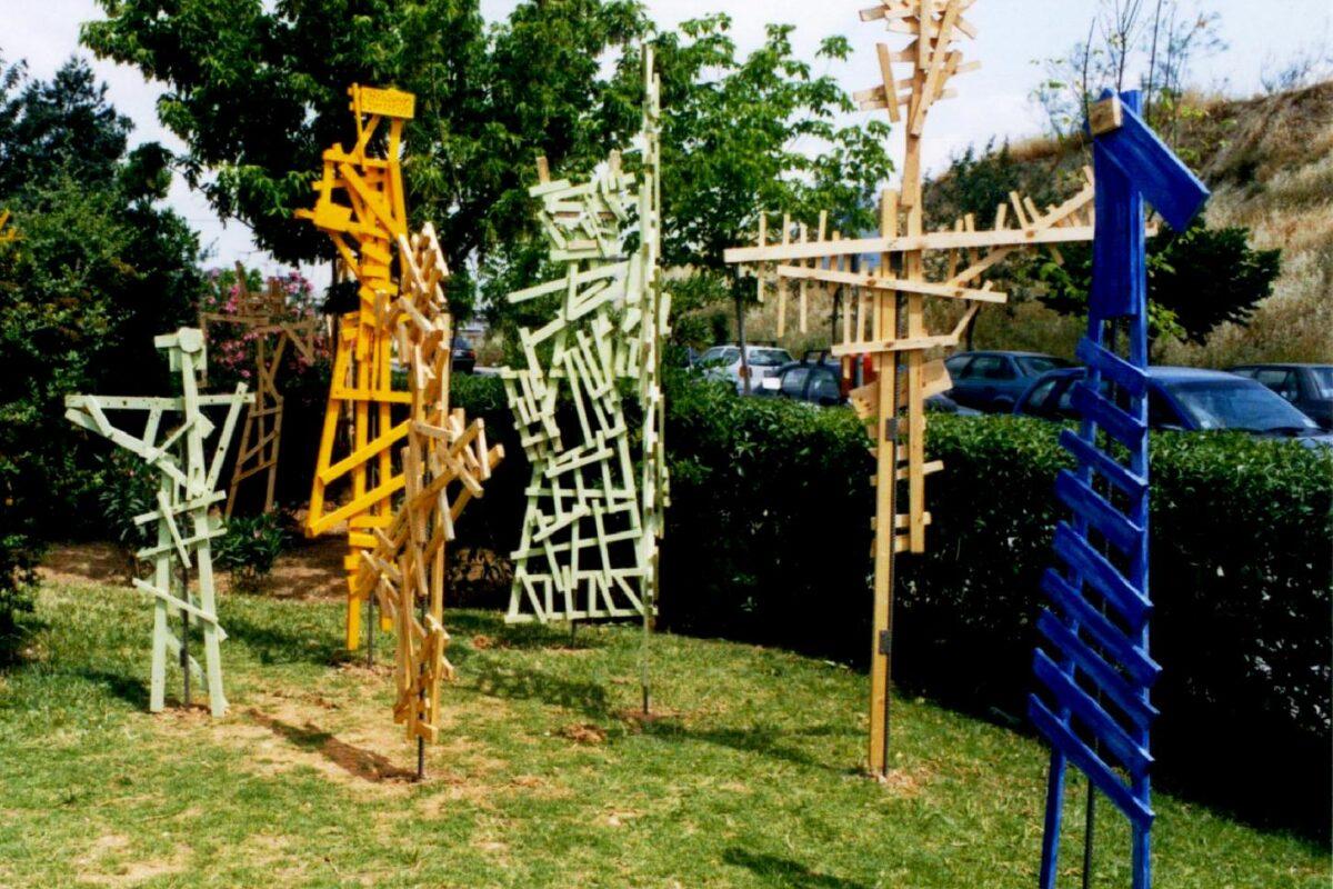 Επτά ξύλινες φιγούρες/γλυπτά είναι μόνιμα στημένες σε τυχαία διάταξη στο αραιό χορτάρι πλατείας που περιβάλλεται από καταπράσινο φράχτη. Οι φιγούρες διαφέρουν σε ύψος από 1,5 έως 2 μέτρα και παριστάνουν διαφορετικές ακαθόριστες μορφές ανθρώπων ή ζώων. Είναι φτιαγμένες από μικρά σανίδια διαφόρων μεγεθών καρφωμένα μεταξύ τους. Δύο φιγούρες είναι μονόχρωμα βαμμένες με έντονο μπλε και κίτρινο χρώμα ενώ οι υπόλοιπες πέντε είναι λευκές ή σε χρώμα φυσικού ξύλου.