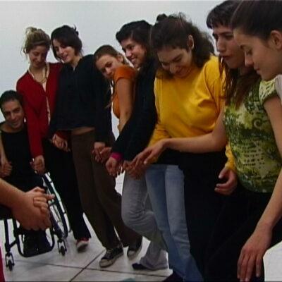 Σε μία αίθουσα 8 κοπέλες στριμώχνονται σε ημικύκλιο η μία δίπλα στην άλλη και παίρνουν παίρνοντας χορευτικές στάσεις, γελώντας. Ανάμεσα τους είναι μισοκρυμμένος ένας νέος άνδρας σε καρότσι.