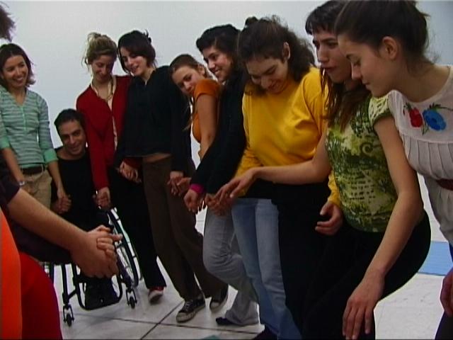 8 νέα κορίτσια στέκονται η μια πολύ κοντά στην άλλη και σπρώχνονται με τους ώμους ώστε να πλησιαστούν ακόμη περισσότερο. Ανάμεσα τους ένας νέος άνδρας καθισμένος σε αναπηρικό καρότσι κλείνει τον κύκλο που σχηματίζεται. Κρατιούνται σχεδόν όλοι από τα χέρια και φαίνονται να διασκεδάζουν πολύ.