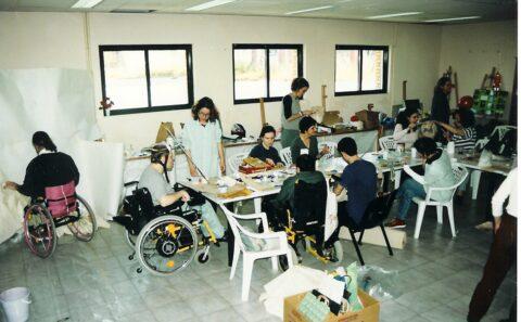 Ένας μεγάλος φωτεινός εργαστηριακός χώρος όπου κυριαρχεί το λευκό, έχει τρία μεγάλα παράθυρα στη σειρά και φορτωμένα ράφια γύρω γύρω. Στη μέση υπάρχει ένα πολύ μακρύ λευκό τραπέζι και γύρω του άλλοι όρθιοι άλλοι καθιστοί σε καρότσια ή λευκές πλαστικές καρέκλες είναι περίπου 12 νεαρά άτομα. Όλοι ασχολούνται με κάποια δική τους εργασία. Ένας άνδρας σε καρότσι ζωγραφίζει φορώντας στο κεφάλι του έναν μονόκερο (ειδικό βοήθημα). Ένας άλλος άνδρας σε καρότσι είναι γυρισμένος προς τον τοίχο και ασχολείται μόνος του με κάτι. Στο κέντρο του πατώματος υπάρχουν ανοιγμένα χαρτοκιβώτια γεμάτα διάφορα υλικά.